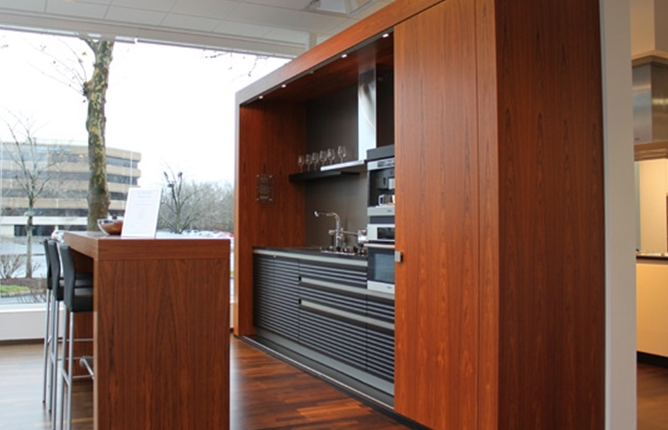 Kitchen storage and appliances hidden in teak cabinet with sliding doors