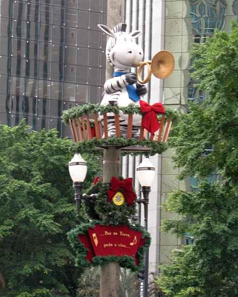 Lamp post X'mas decoration with a zebra carrying a musical instrument on top.